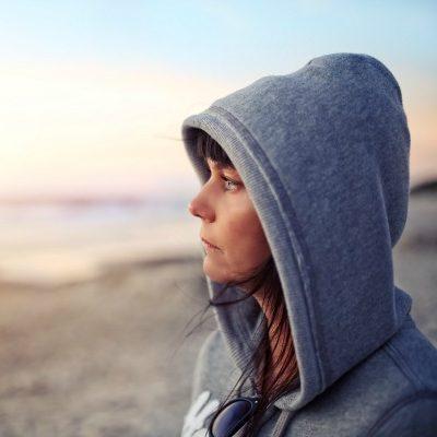 Woman in hoodie on beach