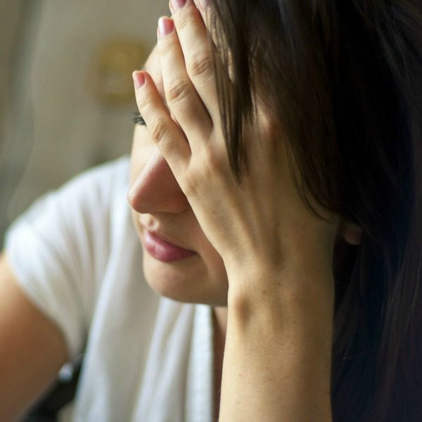 Stressed woman holding forehead