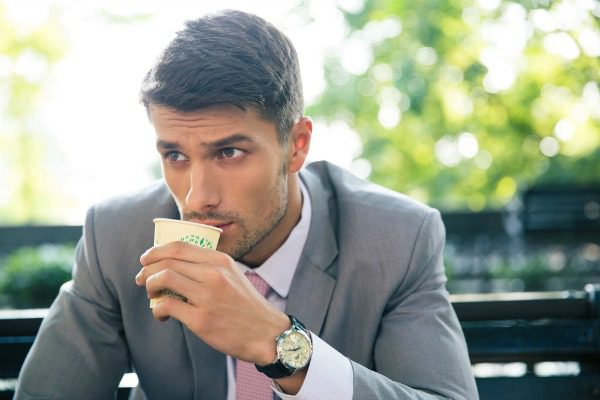 Man drinking coffee on a park bench
