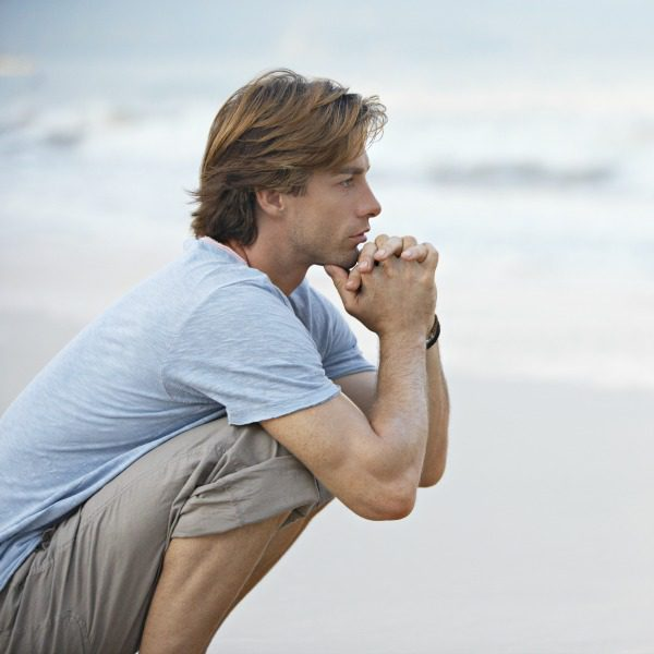 Man practicing mindfulness on the beach