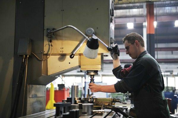 Worker operating drill press
