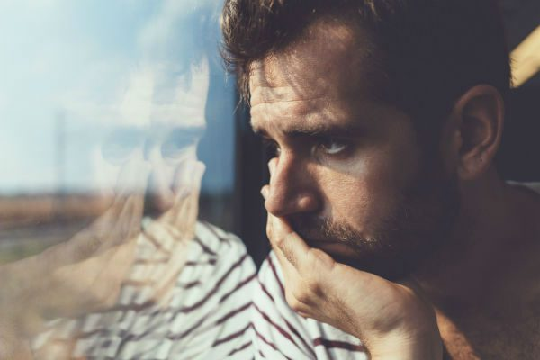 Man by window in deep thought