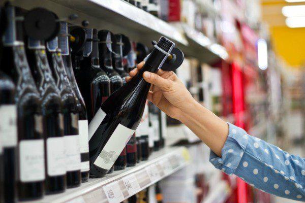 Picking wine bottle from shelf