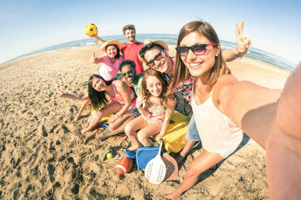 Friends on beach taking selfie