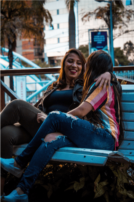 Two women sitting on a bench smiling at each other